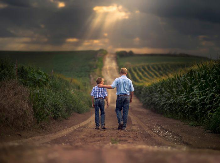 Отец и сын идут по дороге между полей