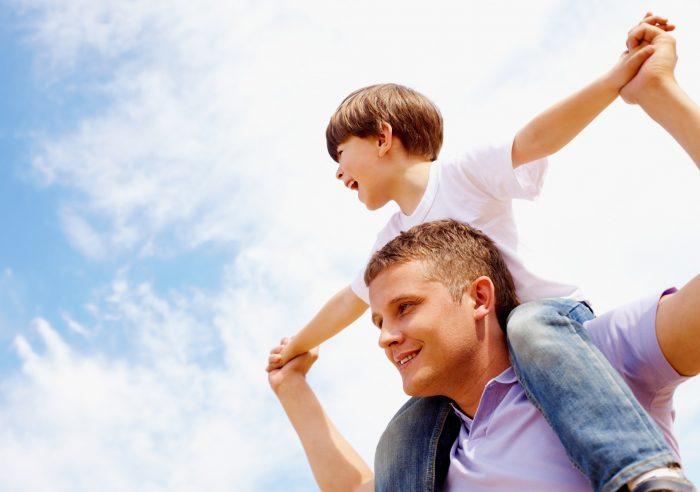 Сын сидит на отцовских плечах