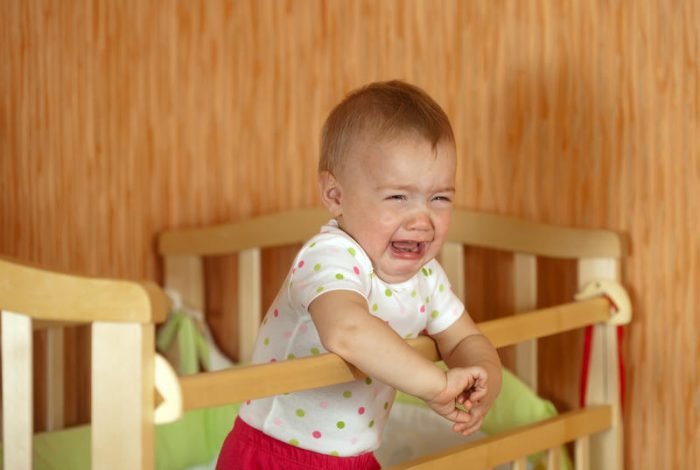 Маленький мальчик стоит в кроватке и плачет
