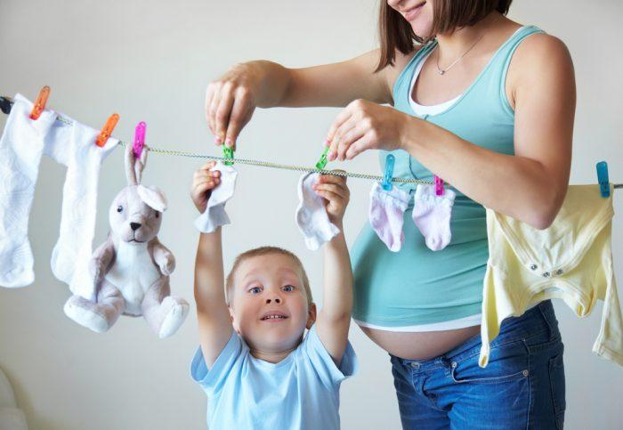Ребёнок помогает маме вешать бельё