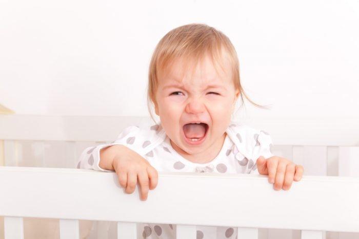 Ребёнок плачет в кровати
