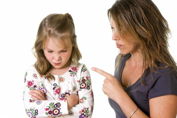 Женщина направляет в сторону девочки, скрестившей руки на груди, указательный палец