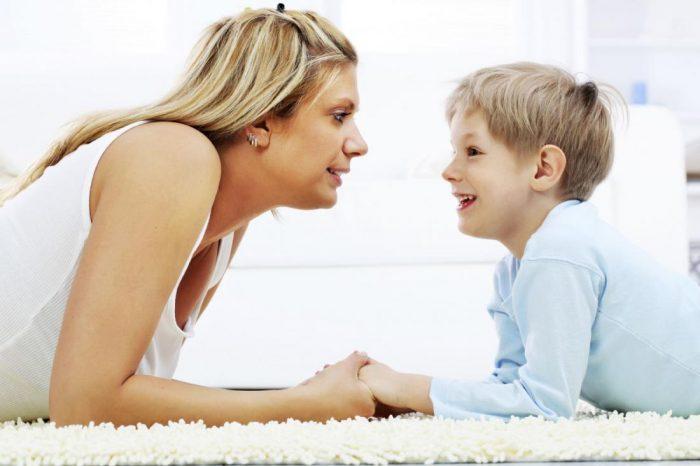 Мама и мальчик лежат на белом ковре, взявшись за руки и глядя друг на друга