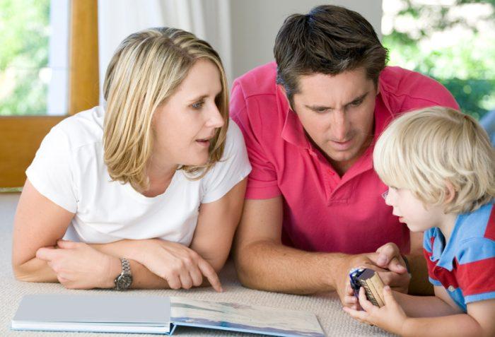 Мама и папа слушают рассказ мальчика, держащего в руках паровозик