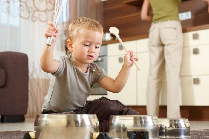 Мальчик играет с кастрюлями на полу, пока мама готовит
