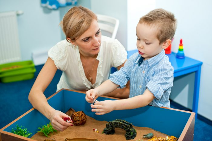 Мальчик и его мама играют с песочнице