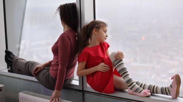 Девочка и женщина сидят на подоконнике
