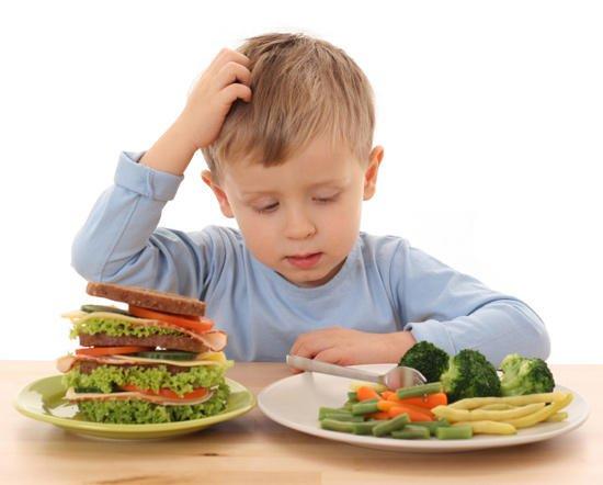 Мальчик выбирает между полезной и вредной пищей