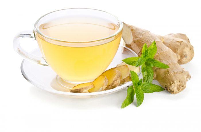 Зелёный чай, рядом на блюдце корень имбиря и его нарезанные дольки