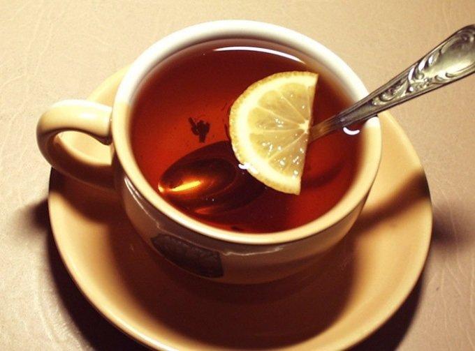 Чёрный чай с половинкой лимона в кружке