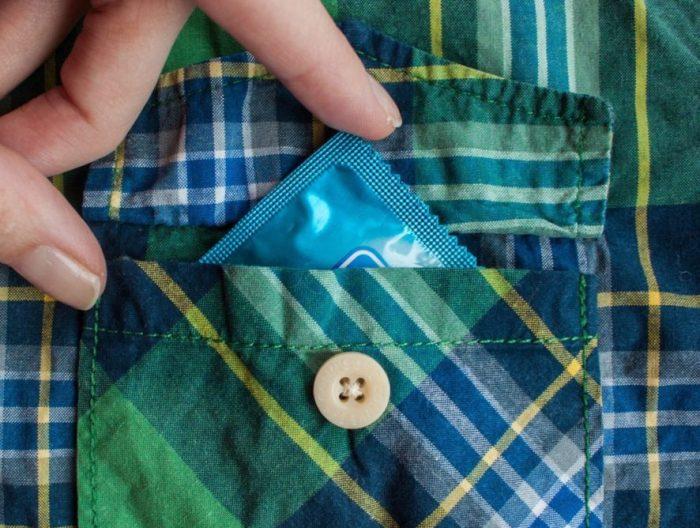 Человек кладёт презерватив в карман