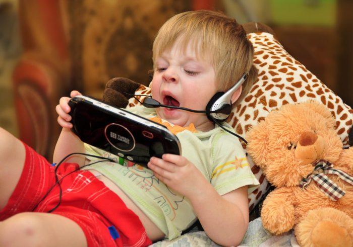 Ребёнок с игровой приставкой и наушниками