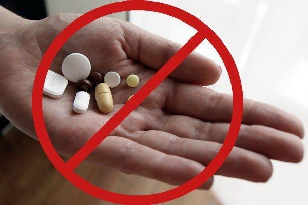 таблетки в ладони под знаком запрета