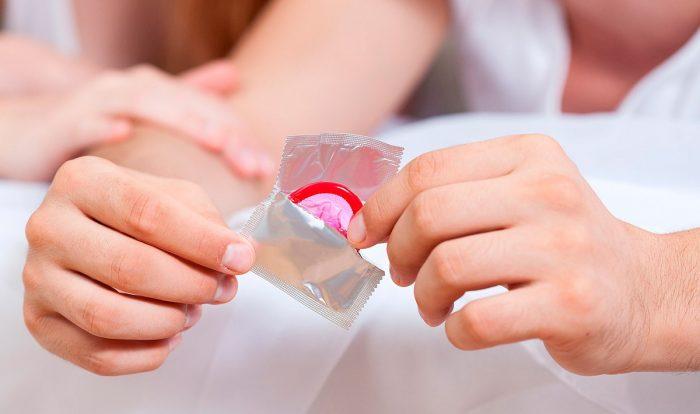 Открытая упаковка с презервативом в мужских руках
