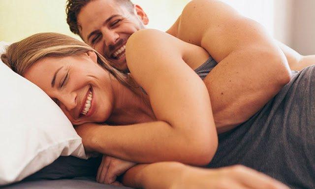 Мужчина в постели обнимает женщину и смеётся