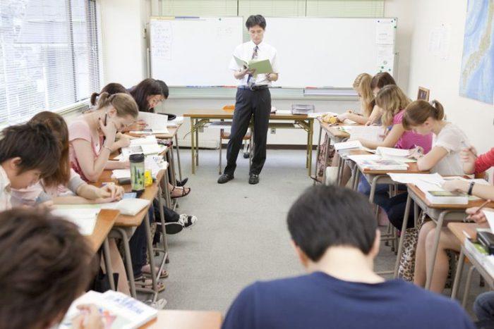 Мужчина стоит в центре класса, окружённый сидящими за партами подростками