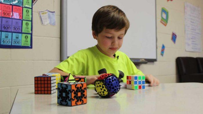 Перед мальчиком на столе лежит кубик рубика и другие головоломки