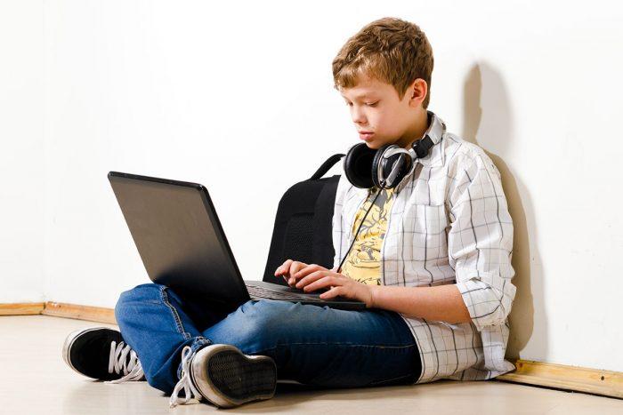 Мальчик сидит на полу, положив ноутбук на колени, и смотрит на клавиатуру