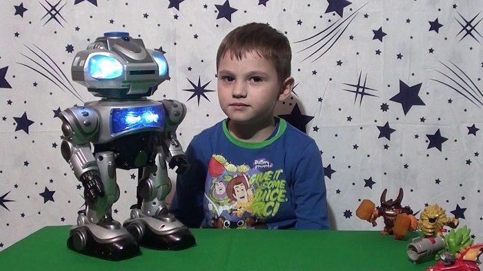 Мальчик сидит за столом, перед ним игрушечный робот