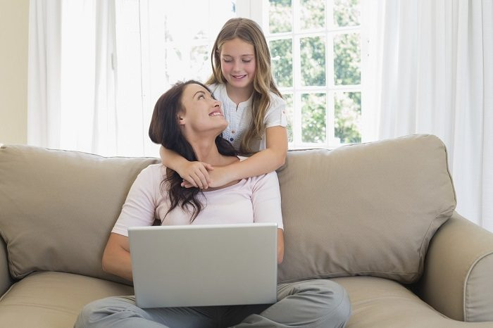 Дочь обнимает маму, сидящую на диване с ноутбуком