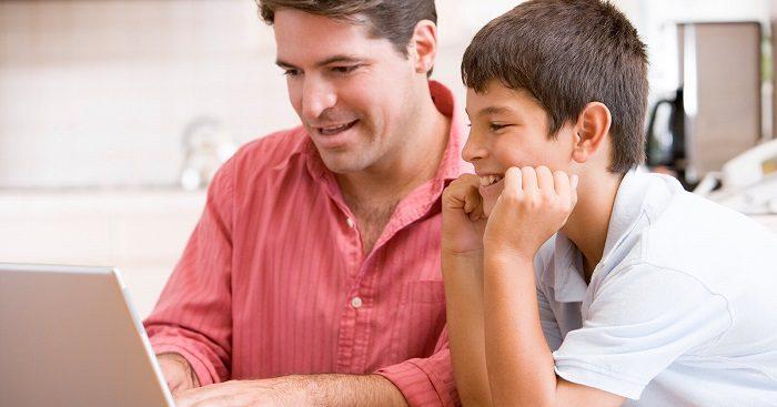 Папа с сыном-подростком вместе что-то смотрят по ноутбуку