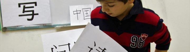 Мальчик смотрит на листок с изображением иероглифа, который держит в руке.