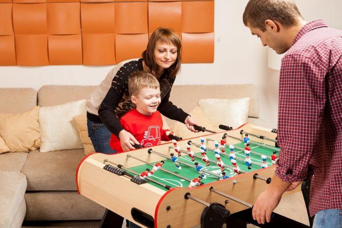 Маленький мальчик с мамой играет против папы в настольный футбол