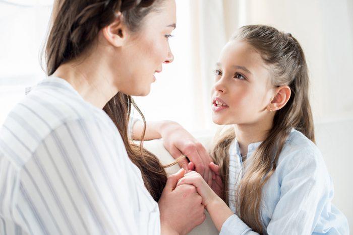 Мама разговаривает с дочкой, они держатся за руки