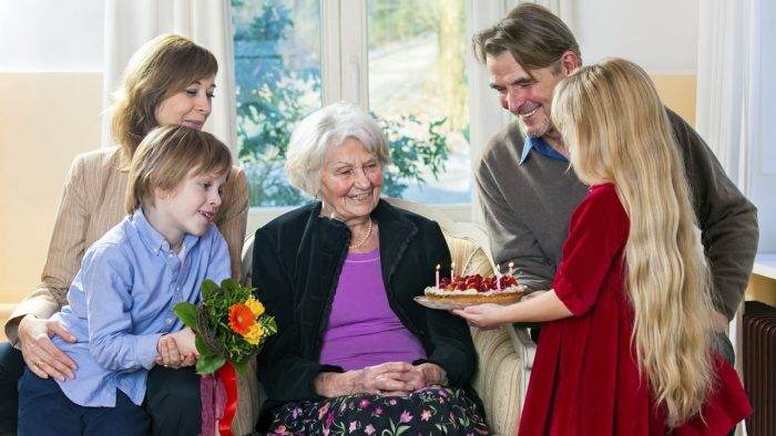 Дети преподносят подарки бабушке — торт и цветы
