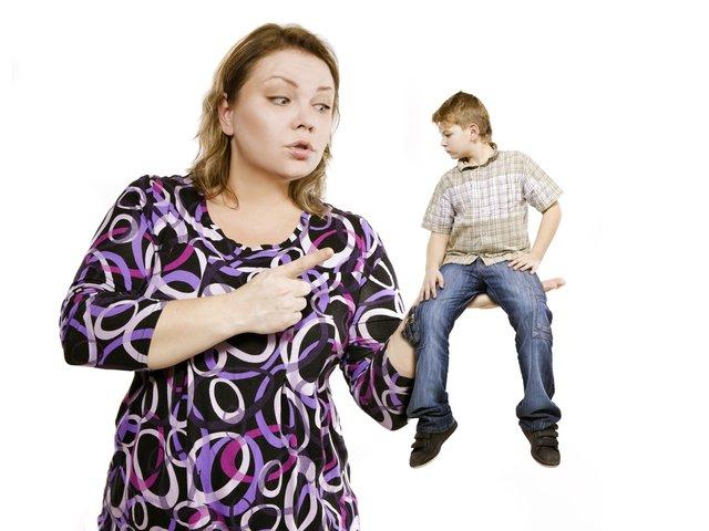 Мальчик сидит на руке у мамы, она грозит ему пальцем