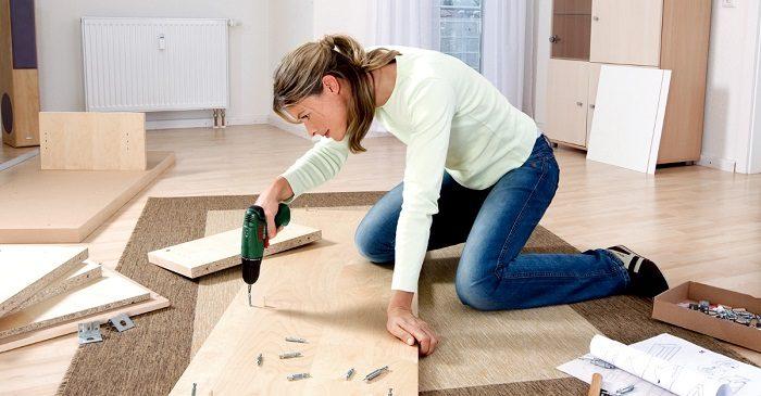 Женщина сама собирает мебель дома