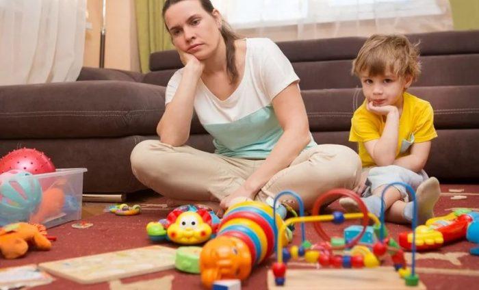 Мама сидит с сыном среди разбросанных игрушек