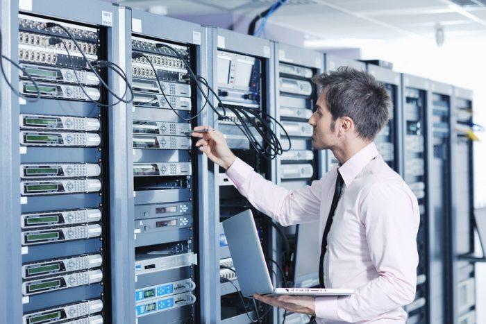 Человек с ноутбуком в руках стоит возле сервера