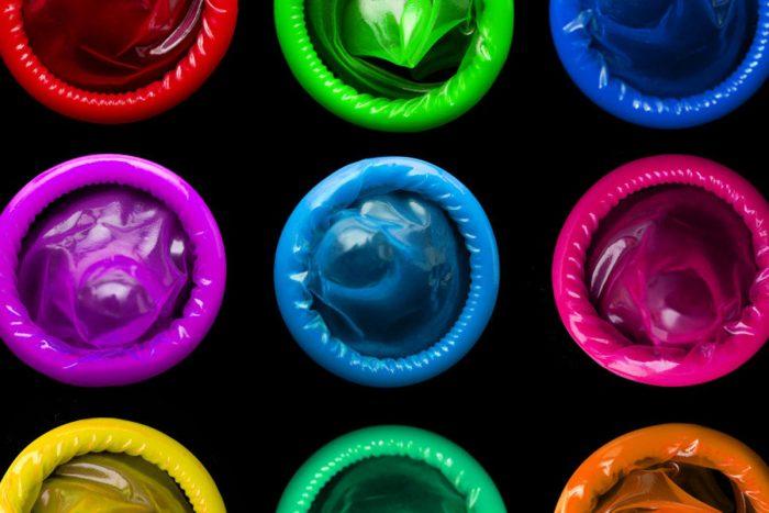 Цветные светящиеся презервативы на тёмном фоне