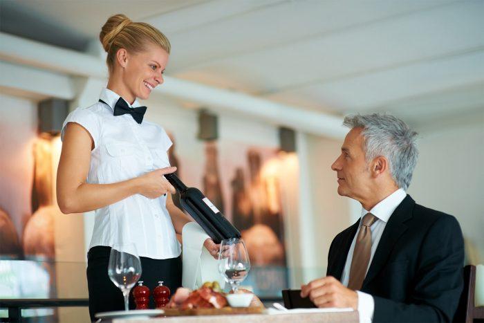 Официант подаёт клиенту бутылку вина