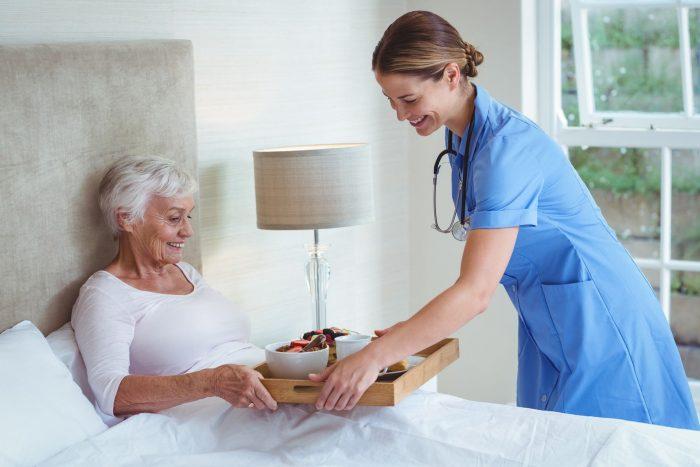 Медсестра подаёт завтрак пациентке