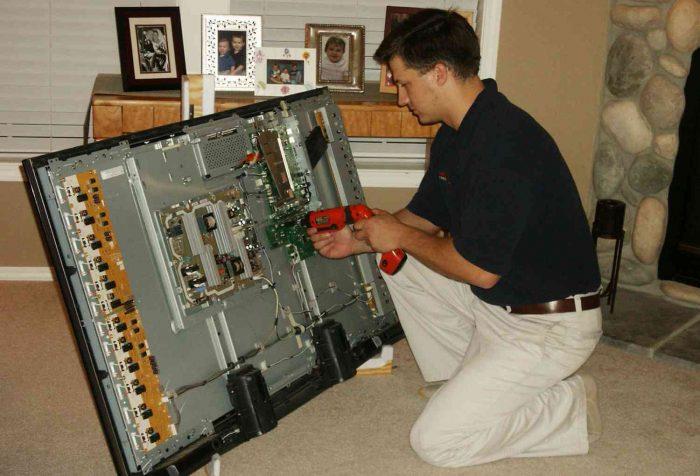 Мастер чинит плазменный телевизор