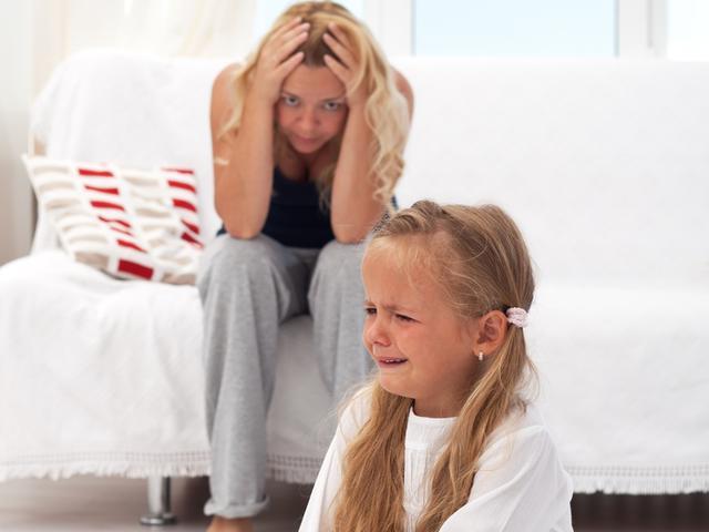 Девочка плачет, мама сидит на диване и держится за голову