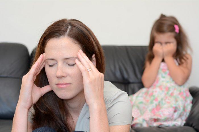 Мама закрыла глаза и держится за виски, дочка плачет на диване