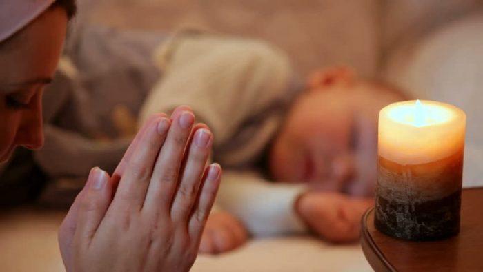 Ребёнок спит, а мама молится перед свечой