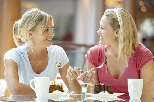 Подруги в кафе едят пирожные