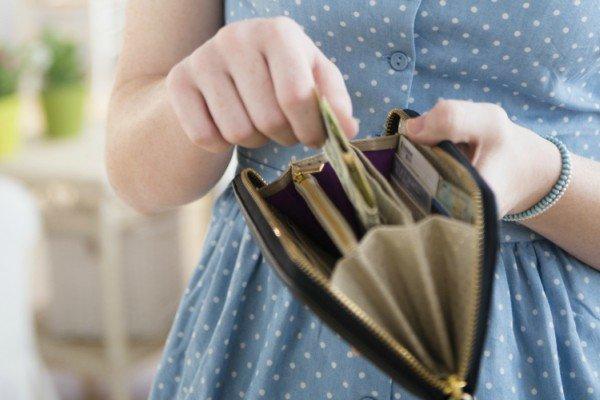 Женщина считает деньги в кошельке