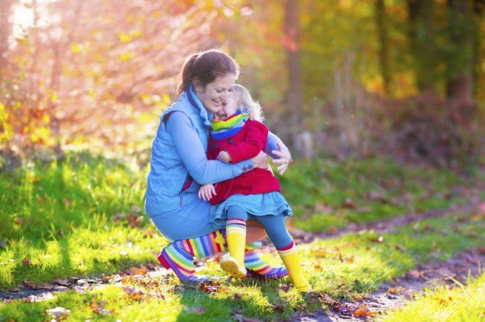 Мама с дочкой гуляют в парке, обнимаются и смеются