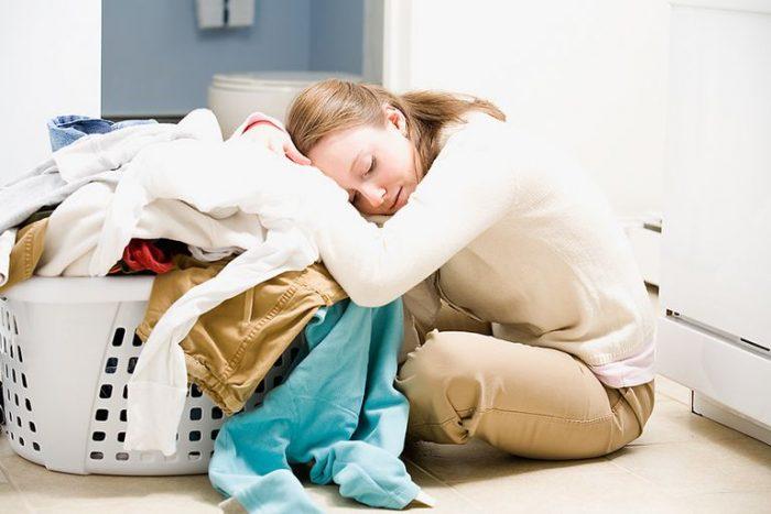 Уставшая женщина облокотилась на корзину с грязным бельём