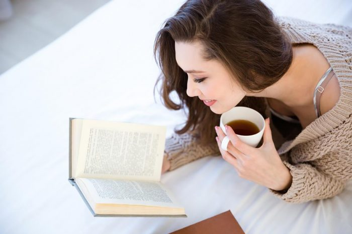 Довольная женщина пьёт чай и читает книгу
