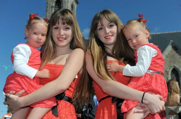 Сёстры-близнецы держат на руках маленьких близняшек