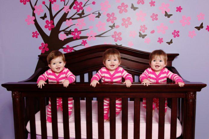 Младенцы-тройняшки стоят в кровати