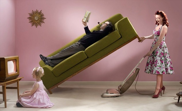 Жена пылесосит, подняв кровать, на которой лежит муж с книгой в руках и сигарой во рту