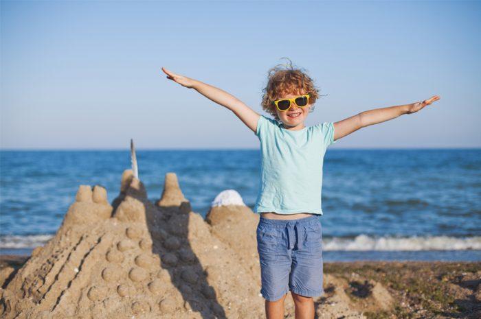 мальчие стоит у моря, вытянув руки в стороны