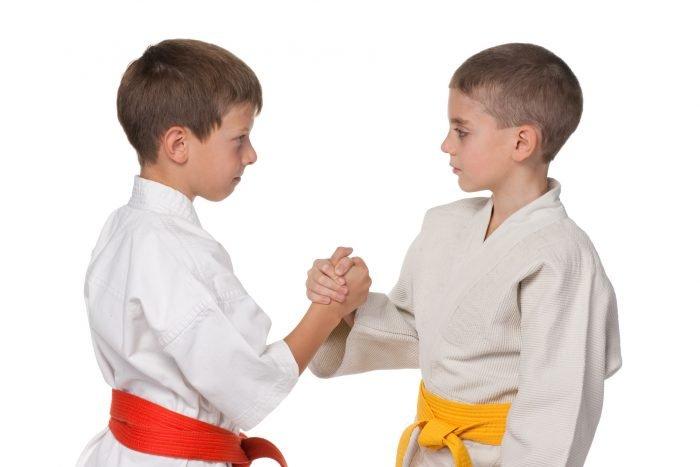 Два мальчика в белых кимоно с красным и жёлтым поясом пожимают руки друг другу